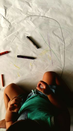 Directly Above View Of Toddler Drawing With Crayons On Paper