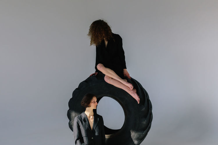 Tire Women Black Color Gray Young Adult Studio Shot Leisure Activity Hairstyle Lifestyles Hair Obscured Face Indoors  Real People Gray Background Contemplation Three Quarter Length Fashion Fashion Photography Girls Females Legs Feet Portrait Portrait Of A Woman Young Women Hair Strange Weird Oddbeauty