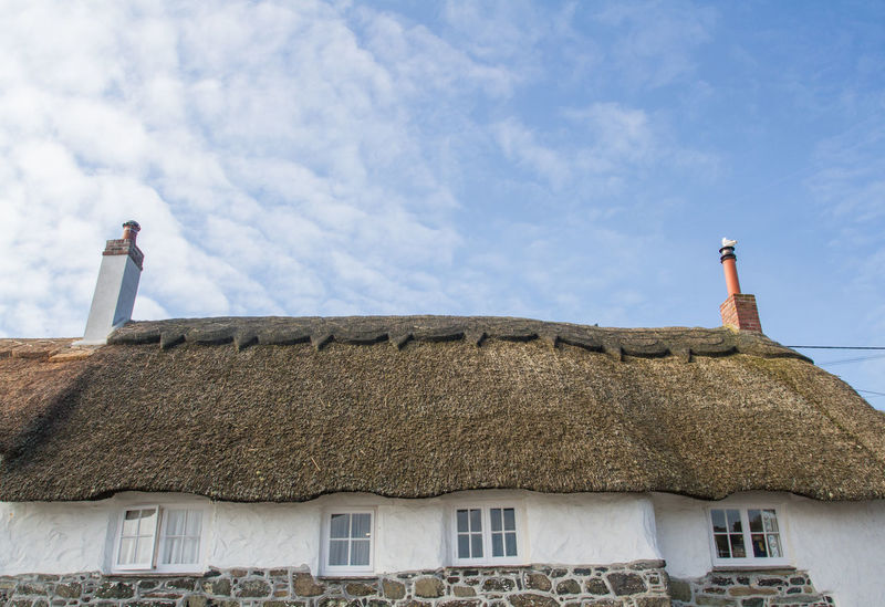 Looking up to the thatched roof and chimney pots of a traditional stone cottage in a small, Cornish village .Architecture Building Exterior Built Structure Day Low Angle View Nature No People Outdoors Roof Sky Thatched Roof Cottage Cottage Life Cottages Thatch Thatched Cottage Chimneys Uk England Britain Picturesque Quaint  Village Traditional Facades