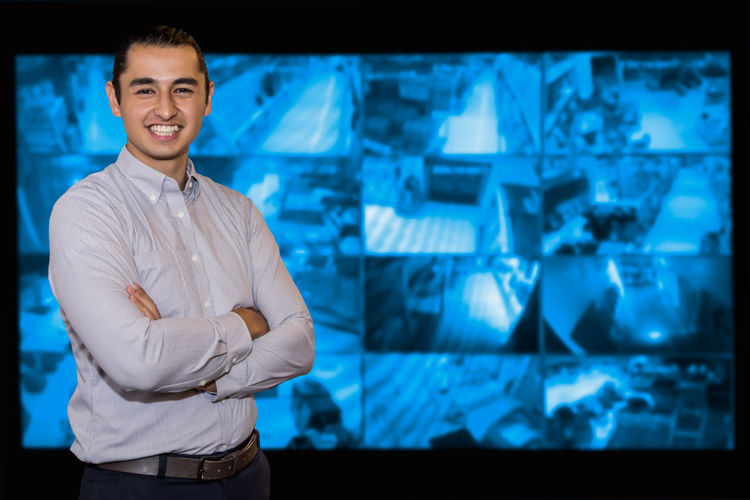 Confident young man in the CCTV system. Adult Blur Blurry Camera Cctv Computer Computerized Control Dark Desk Footage  Guard Holding Indoors  Keyboard Lcd Looking Male Mature Men Monitor Night Office Operator Panel person Pointing Protection Radio Record Room Safety Screen Secret Secure Security Side Sitting Spy Steal Surveillance System Talkie Technology Thief Using Video View Walkie Working