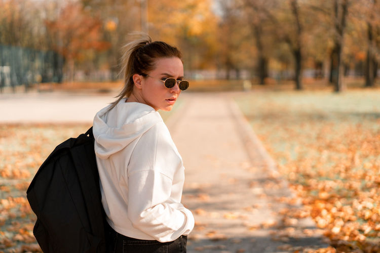 Portrait of woman wearing sunglasses while standing on footpath during autumn
