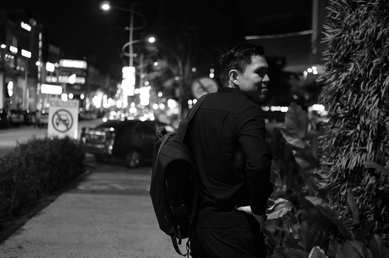Smiling man looking away by tree in city at night