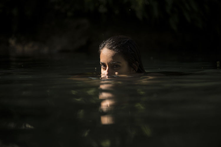 Portrait of young woman swimming in lake