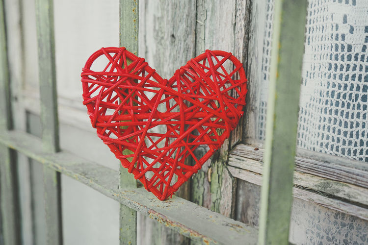 Close-up of red heart shape on metal fence