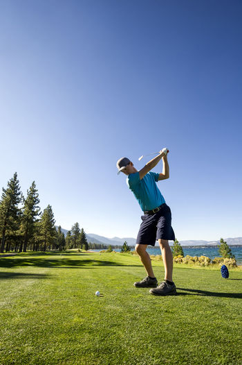 Full length of man standing on golf course against clear sky
