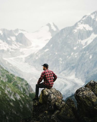 Rear view of person standing on rock against mountains