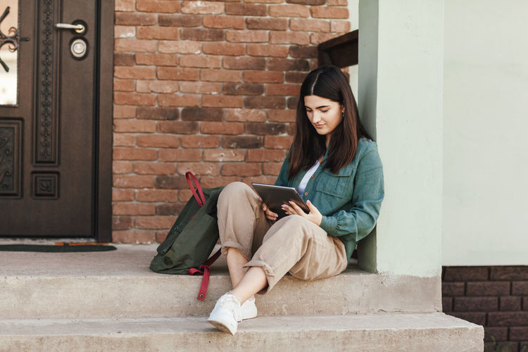 Young female student sitting on steps and studying with tablet in college or private school