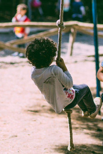 Rear view of boy hanging with rope in playground