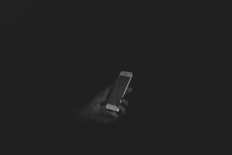 Close-up of hand holding smart phone against black background