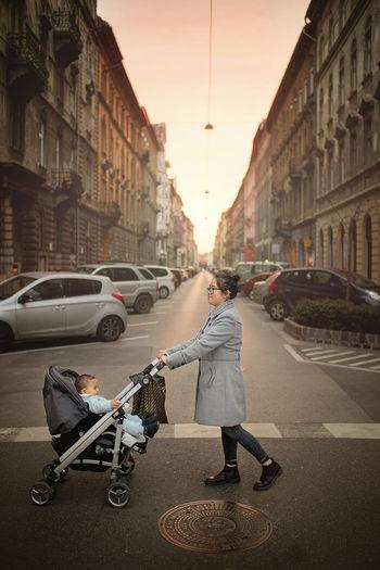 Woman pushing stroller on street