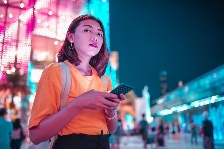 Portrait of woman using mobile phone in city at night
