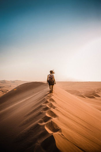 Rear view of woman walking on sand dune in desert