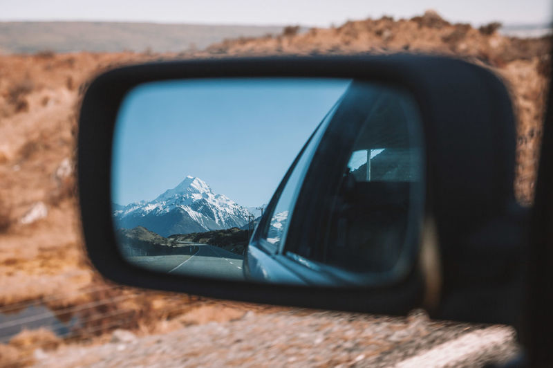 Reflection of snowcapped mountain on side-view car mirror