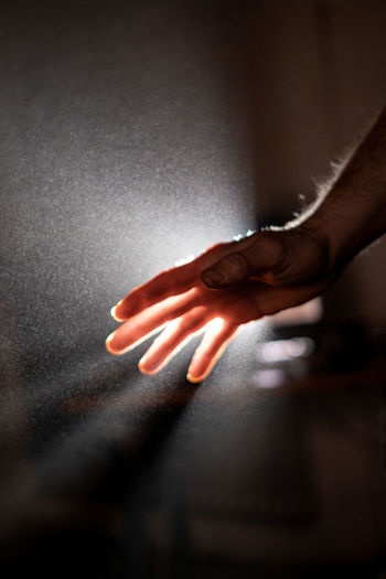 Close-up of human hand touching cross