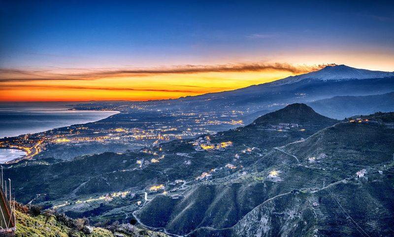 Fantastic view of Mount Etna at sunset with lights of the cities at its feet. Sunset Landscape Silhouette First Eyeem Photo Sky Nature Day Outdoors Beauty In Nature Clouds City Sea Volcano Light Mountain Dusk Scenics Horizon Sicily Nikon No People Astronomy EyeEmNewHere
