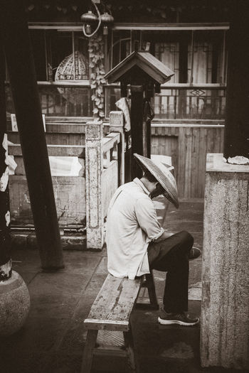 Side view of man sitting on seat in city