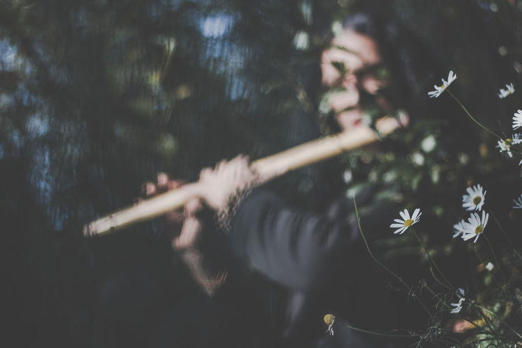 Artist Man Music Nature Adult Close Up Close-up Day Ethnic Ethnic Music Ethnic Tools Flower Flowering Plant Forest Growth Headshot Holding Human Body Part Land Leisure Activity Lifestyles Musician Nature One Person Outdoors Plant Playing Real People Selective Focus Tree Women