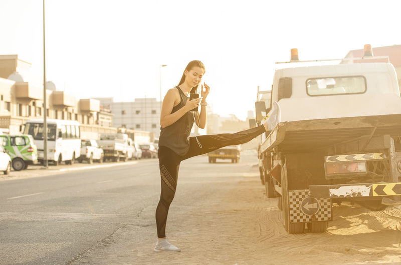 Athletic beautiful white female fitness model wearing long black sports wear with earphones connected to a mobile phone stops to stretch in a urban street with trucks and sun flare in the background Earphones Stretching Legs Beautiful Woman Fitness Training Fitnessmodel Long Hair Sports Clothing Sportswear Sun Flare Trunk