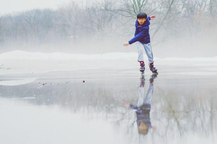 Full length of boy skating on snow covered land