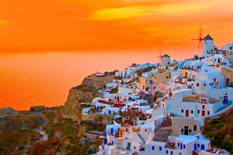 Oia, Santorini, Greece Windmill Architecture Beauty In Nature Building Exterior Built Structure City Cityscape Day High Angle View Nature Oia Outdoors Residential Building Santorini Scenics Sea Sky Sunset Town Travel Destinations Tree Water