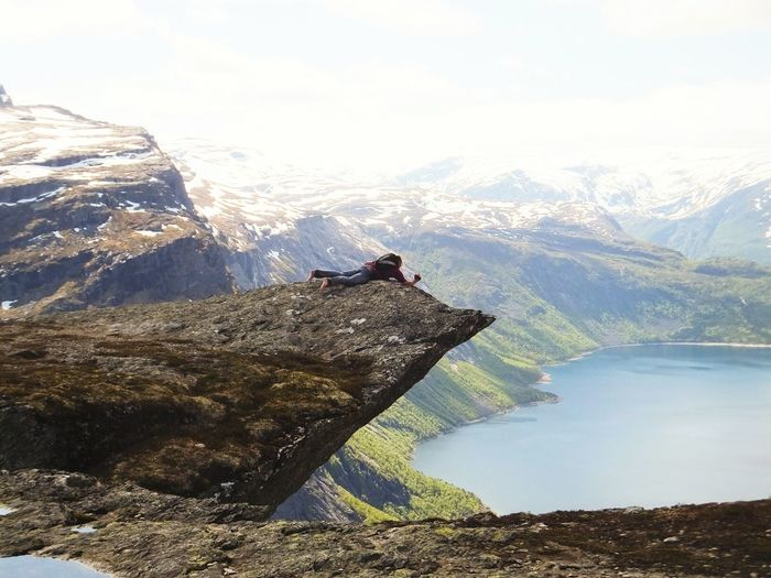 Man Lying On Cliff Over Lake Against Sky