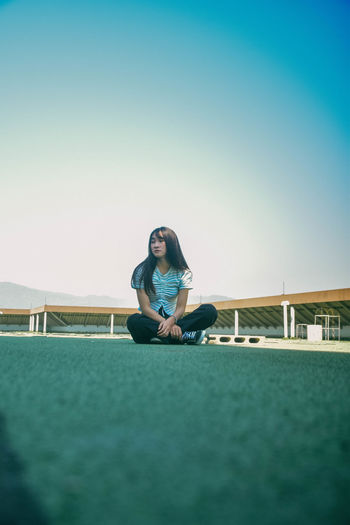 Full length of young woman sitting on floor at building terrace