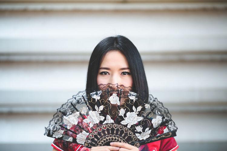 Portrait Of Woman With Folding Fan Against Wall