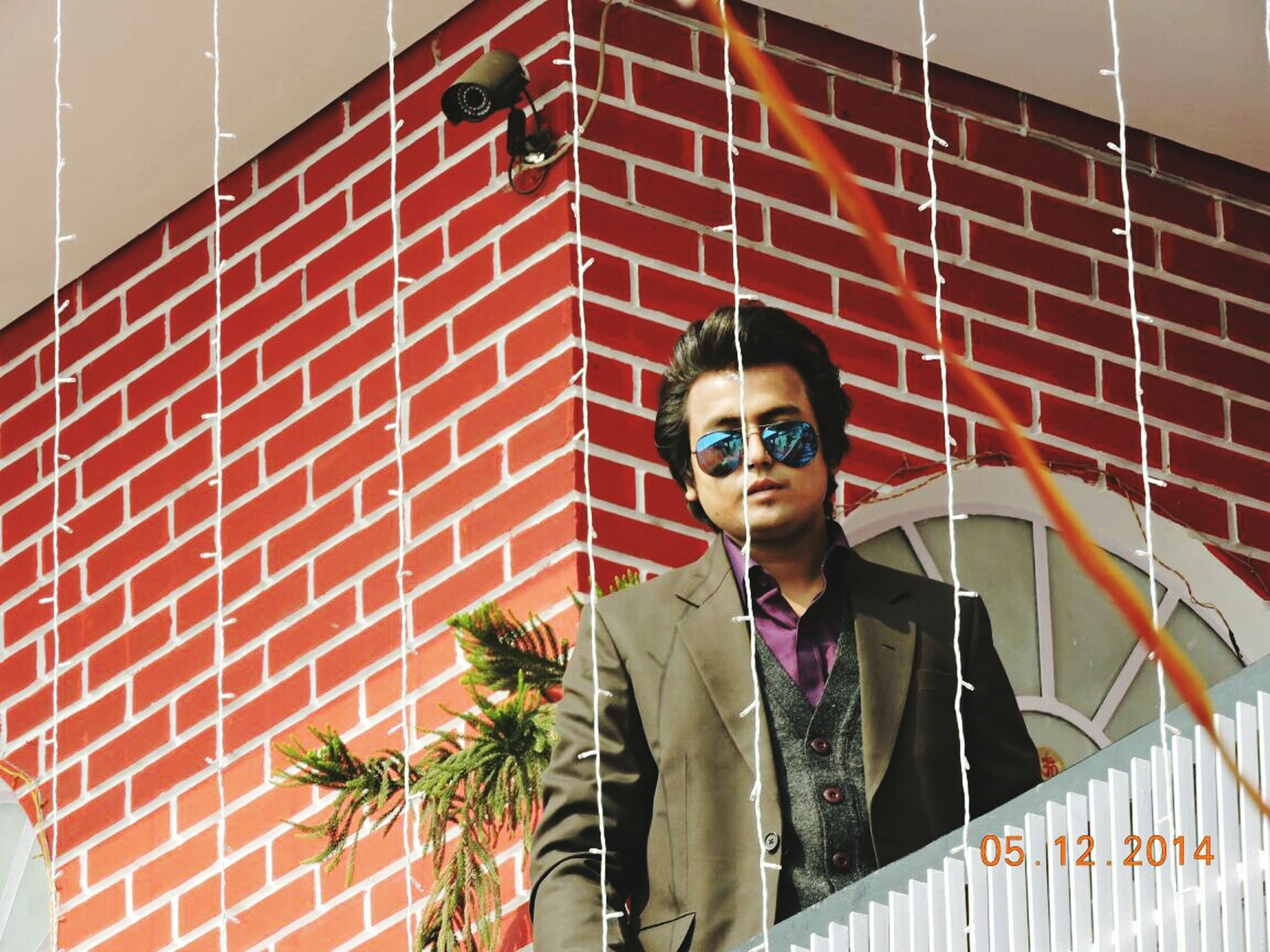 looking at camera, portrait, person, young adult, lifestyles, front view, casual clothing, leisure activity, young men, smiling, standing, happiness, wall - building feature, indoors, sunglasses, built structure