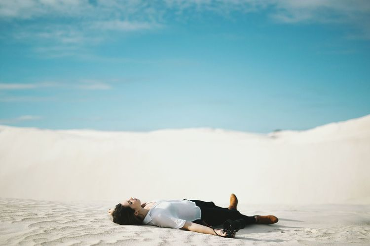 Full length of woman holding camera lying on sand at desert against sky
