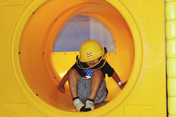 Cute boy playing in yellow tunnel slide