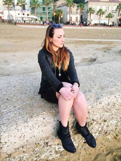 Young Woman Sitting On Retaining Wall At Beach