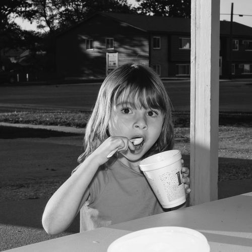 Portrait of girl eating outdoors