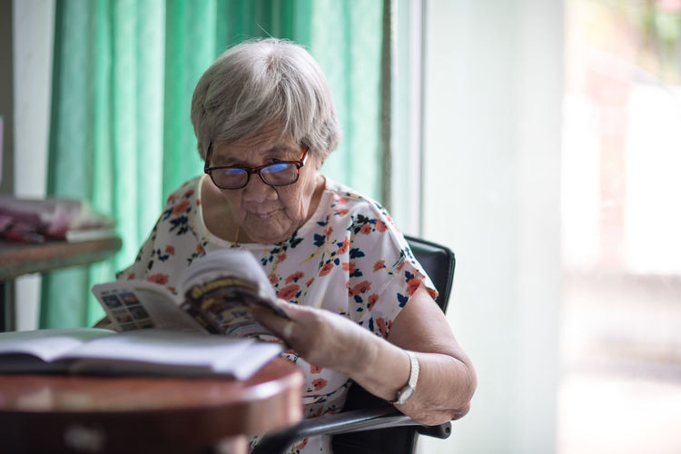 Woman reading book on table