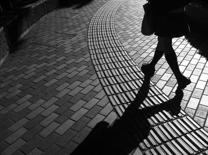 Low section of silhouette woman walking on sidewalk
