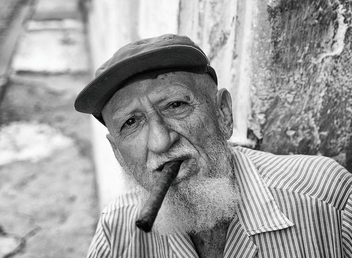 Portrait of senior man wearing cap smoking cigar