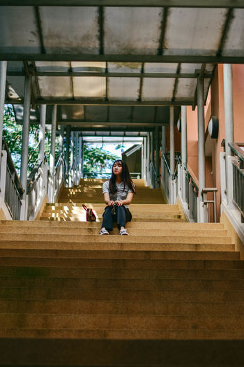 Full length of young woman sitting on staircase at building