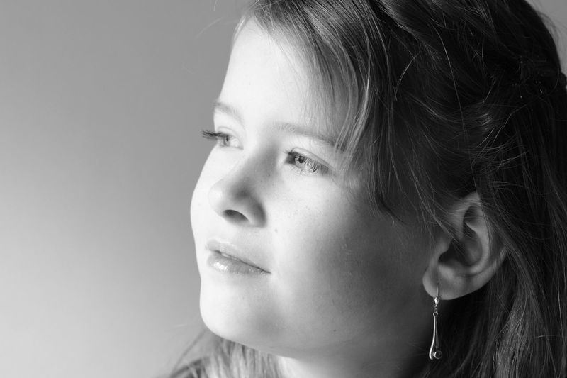 Close-up of thoughtful girl looking away against wall