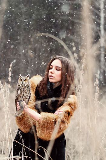Young woman holding owl