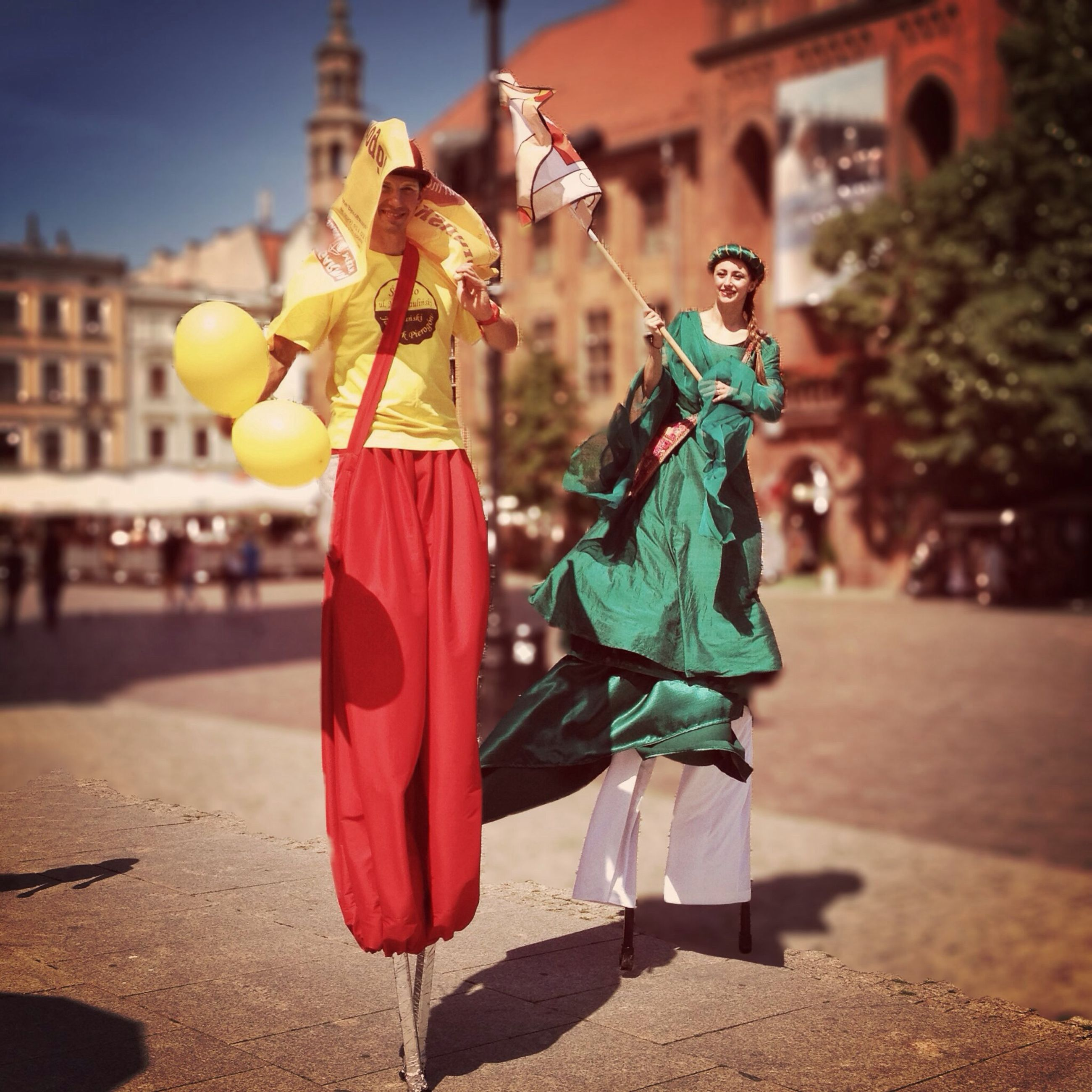 focus on foreground, lifestyles, full length, building exterior, leisure activity, built structure, architecture, street, casual clothing, cultures, incidental people, holding, tradition, traditional clothing, day, sunlight, celebration, outdoors