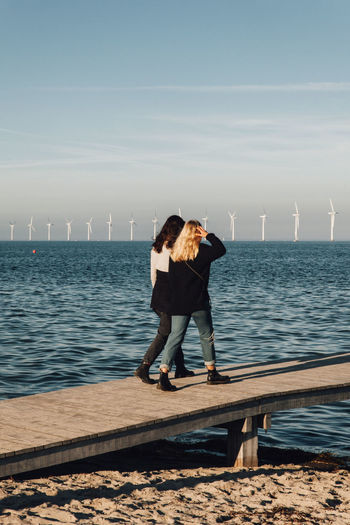 Friends walking on pier over sea against sky