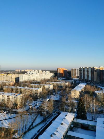 High angle view of snow covered buildings against blue sky