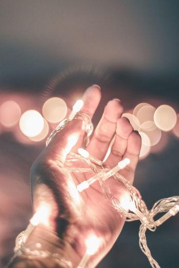 Close-up of hand holding illuminated lights