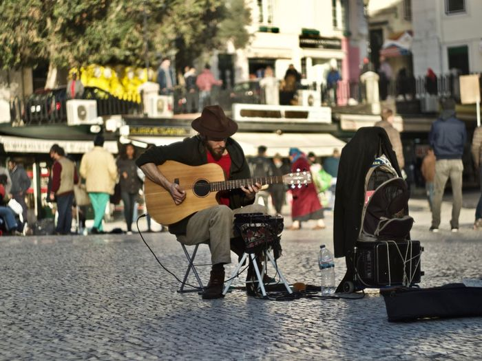 Musical Instrument Musician Artist Music Incidental People Men Performance Street Street Performer Sitting Musical Equipment Real People City Group Of People Playing Arts Culture And Entertainment Full Length String Instrument Skill  Street Musician Entertainment Occupation