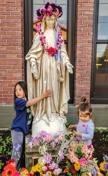 Girl With Sister Standing By Virgin Mary Statue