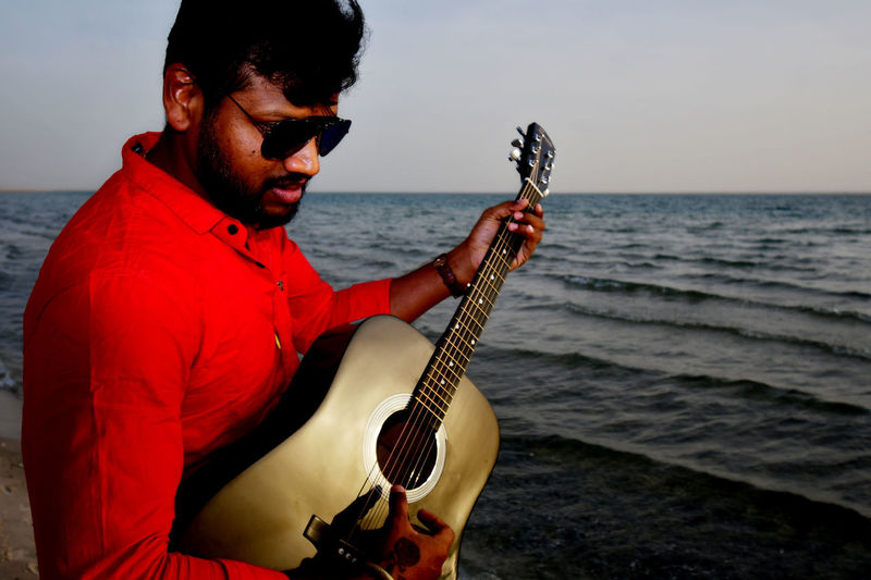 Guitar man in a red shirt has a black guitar and playing music on the beach Acoustic Beach Life Beach Photography Guitar Time Red Acoustic Guitar Day Guitar Guitar Love Guitar Man Guitar Player Guitarist Guitars Horizon Over Water Music Musical Instrument Musician One Person Outdoors Playing Real People Red Color Red Shirt Sea Young Adult