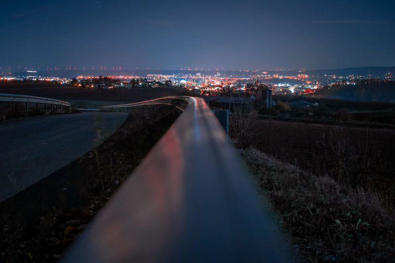 Light trails on road by illuminated city against sky at night
