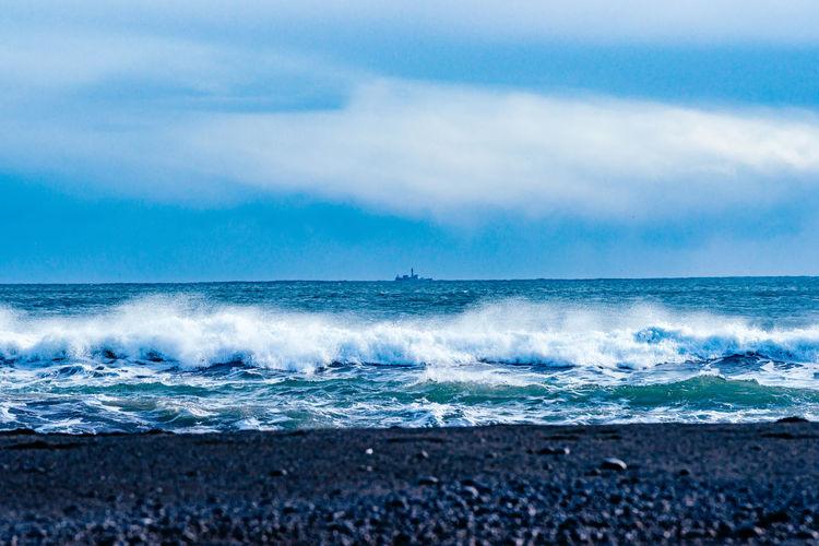 Scenic view of splashing water in sea against sky