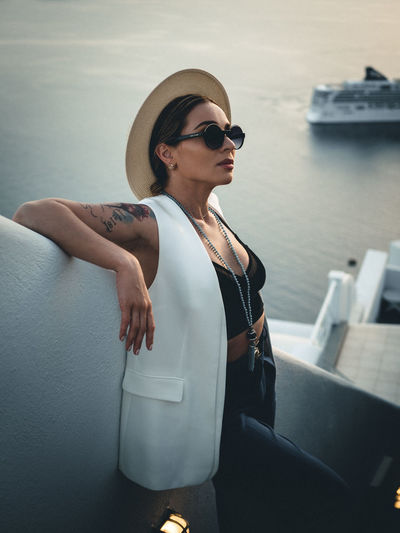 Woman wearing sunglasses looking away while standing on staircase