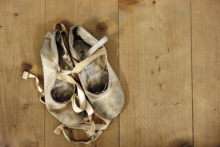 Close-up of dirty ballet shoes on hardwood floor