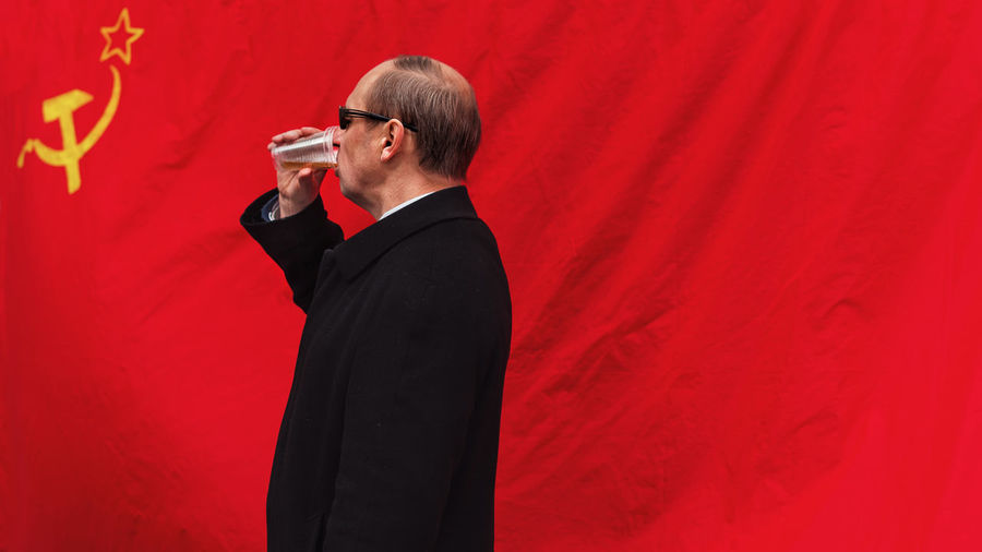 Side view of man drinking beer against former ussr flag